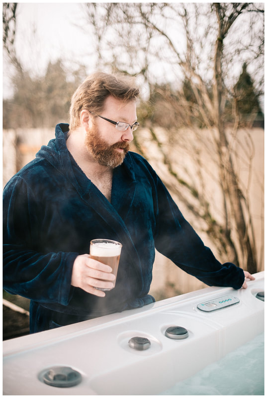 Man with beard in robe standing by hot tub drinking beer for dudeoir photoshoot.